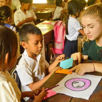 Voluntaria social enseñándole a un niño los colores durante su proyecto en Camboya.